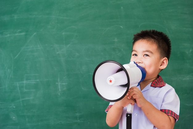 De volta à escola. asiático engraçado criança fofa menino do jardim de infância da pré-escola com uniforme de estudante falando no megafone
