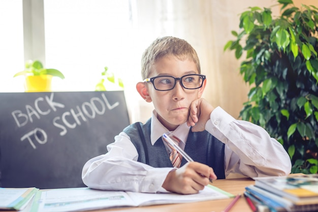 De volta à escola. bonita criança sentada na recepção na sala de aula.