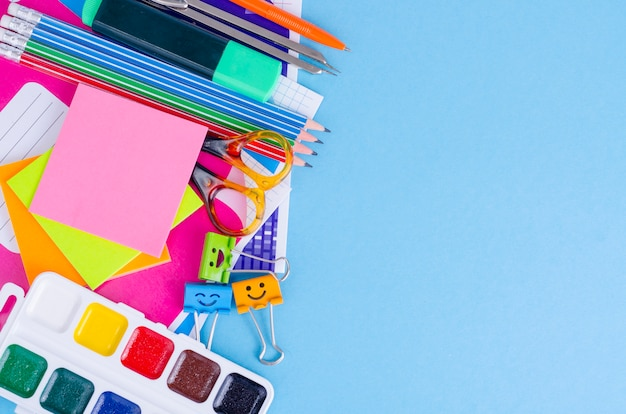 De volta à escola com acessórios das escolas - pinturas, lápis, cadernos, tesouras, marcadores, fundo azul.