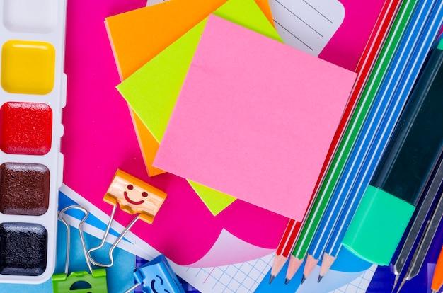 De volta à escola com acessórios escolares - tintas, lápis, cadernos, tesouras, marcadores, azul.