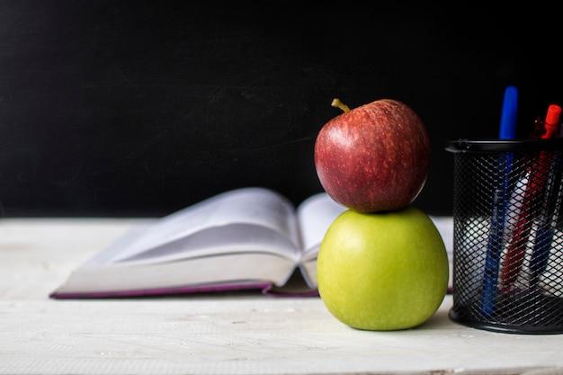 De volta à escola, conceito de educação e conhecimento, apple e livro de nota na frente da tabela quadro negro
