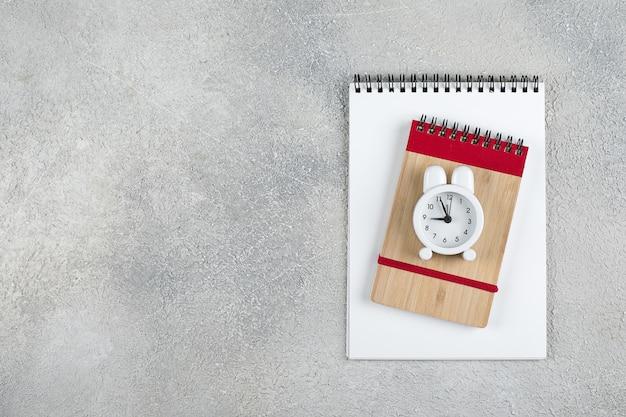 De volta à escola. conceito mínimo de tempo escolar. bloco de notas, lápis, despertador. vista plana, vista superior