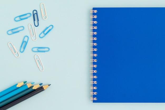 De volta à escola criativa. caderno azul com lápis e grampos em uma ideia superior do fundo azul de uma configuração lisa.