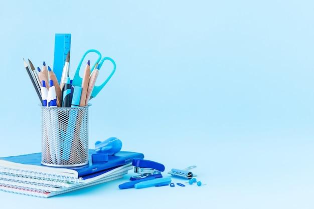 De volta à escola e ao conceito de educação papelaria para estudar em um fundo azul e local para texto