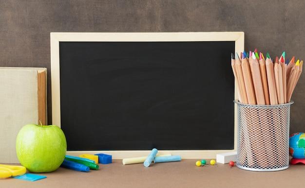 De volta à escola e ao conceito de educação papelaria para estudos lousa maçã verde e lugar para texto