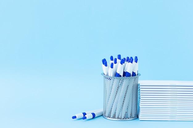 De volta à escola, educação e conceito de negócio papelaria para estudar pilha de cadernos e um conjunto de canetas em um suporte sobre um fundo azul e local para texto