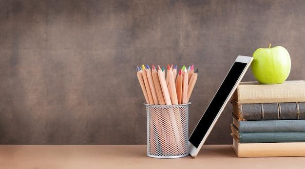 De volta à escola, educação e conceito de negócios acessórios para estudar um conjunto de lápis de madeira em uma pilha de livros e maçã verde perto do quadro-negro. conceito de educação