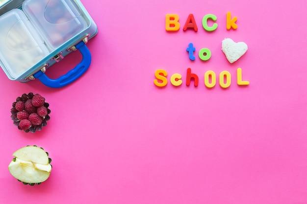 De volta à escola escrevendo perto de frutas e lancheira