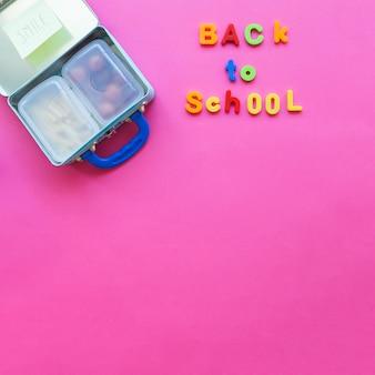 De volta à escola escrevendo perto de lancheira