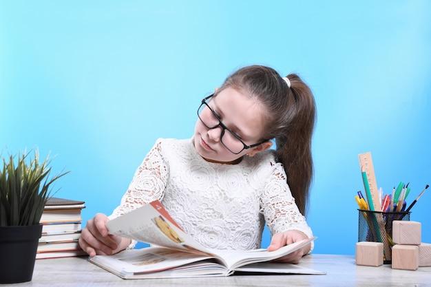 De volta à escola . feliz criança trabalhadora bonito está sentado em uma mesa dentro de casa. garoto está aprendendo em sala de aula. carantine. garoto está aprendendo em casa.
