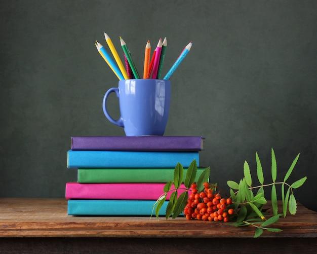 De volta à escola. lápis de cor, livros didáticos e bando de rowan na mesa.