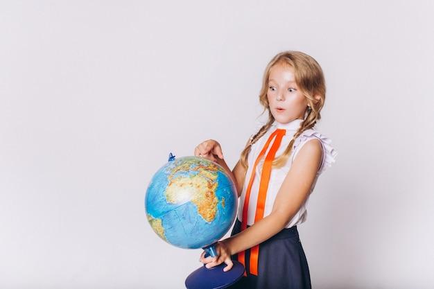 De volta à escola. linda adorável loira loira com globo em uniforme escolar em fundo branco