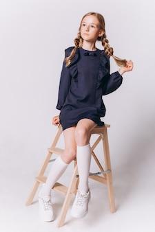 De volta à escola. linda adorável loira loira com uniforme escolar em fundo branco