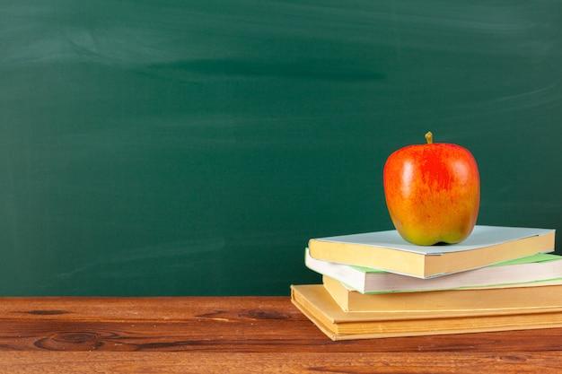 De volta à escola - maçã e livros com lápis e lousa