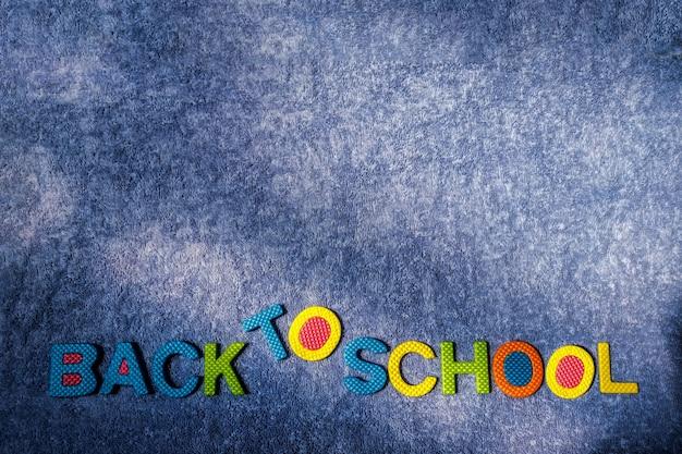 De volta à escola. material de cortiça colorida em um fundo de pano azul
