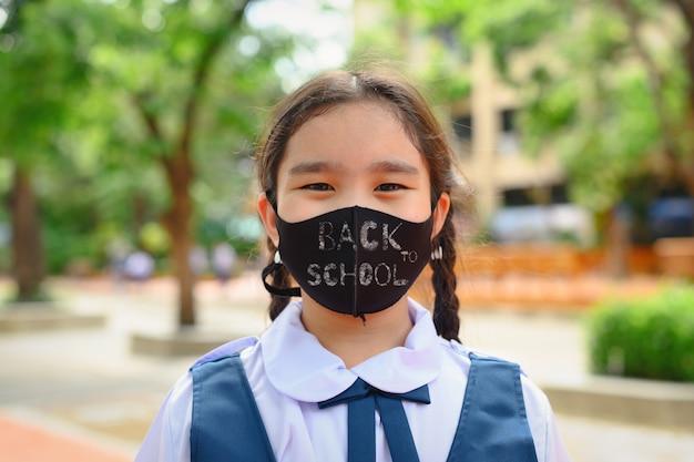 De volta à escola. menina criança asiática usando máscara facial com mochila, indo para a escola. pandemia de coronavírus. novo estilo de vida normal. conceito de educação.