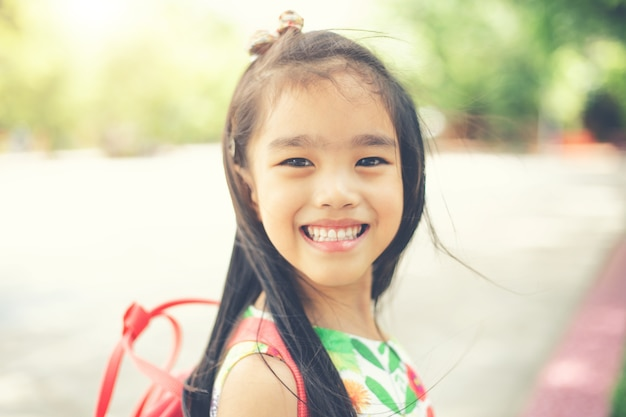 De volta à escola. menina de sorriso feliz da escola primária na jarda de escola.