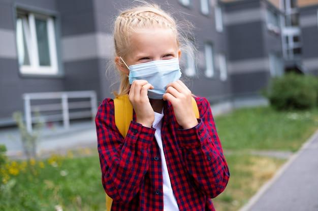 De volta à escola. menina usando máscara e mochilas para proteger e proteger contra o coronavírus. criança indo para a escola após o fim da pandemia.