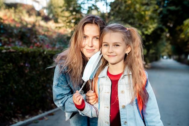 De volta à escola. no outono, uma menina de 7 anos, acompanhada de uma jovem mãe de família, vai para a escola usando máscaras.