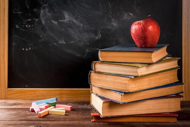 De volta à escola. setembro. lousa de ardósia com giz para desenho, maçã, livros ... copyspace