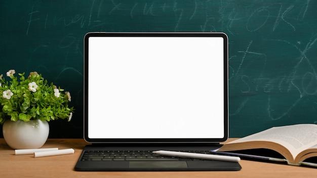 De volta à escola. tablet digital com teclado mágico e caneta stylus na mesa de estudo de madeira com livro aberto, giz, planta sobre lousa verde