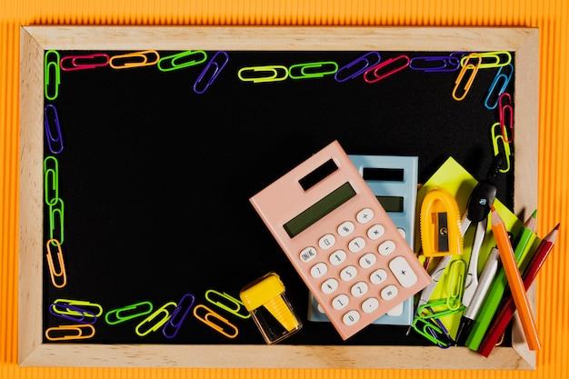 De volta ao conceito da escola. equipamento de educação na lousa em fundo laranja.