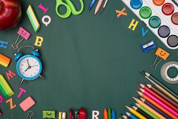 De volta ao conceito de compras da escola. foto da visão superior acima de papel de carta colorido e uma maçã isolada no greenboard