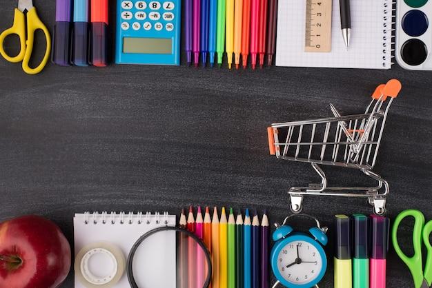 De volta ao conceito de compras de artigos de papelaria da escola. início do conceito de estudos. acima, foto de visão aérea de um pequeno carrinho de maçã e papel de carta colorido isolado no quadro-negro com copyspace