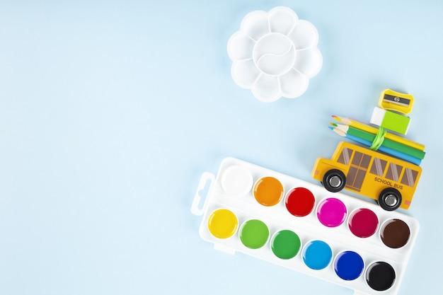 De volta ao conceito de escola. acessórios de desenho. ônibus escolar de brinquedo leva aquarela, sobre fundo azul. vista do topo. copie o espaço