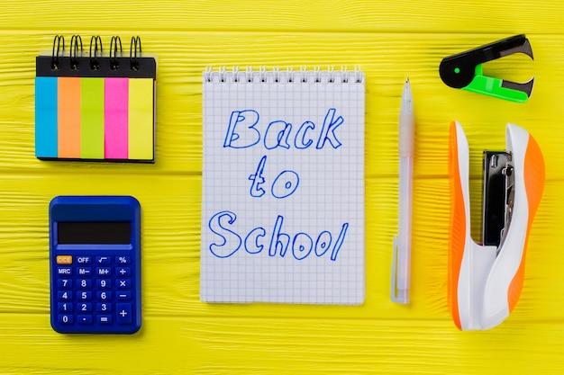 De volta ao conceito de escola. bloco de notas com caneta, calculadora e outros acessórios.
