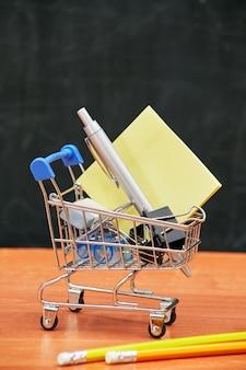 De volta ao conceito de escola, carrinho de compras com material de escritório sobre o conselho escolar, universidade, faculdade, espaço de cópia,