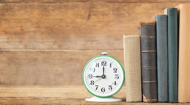 De volta ao conceito de escola e educação a pilha de livros e despertador no fundo de madeira e lugar para texto