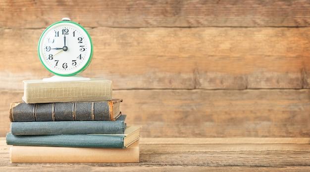 De volta ao conceito de escola e educação a pilha de livros e despertador sobre o fundo de madeira e lugar para texto
