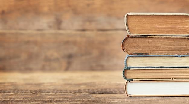 De volta ao conceito de escola e educação a pilha de livros sobre o fundo de madeira e lugar para texto