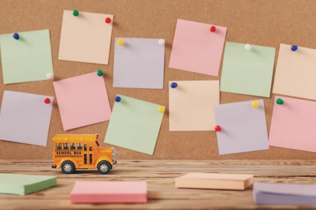 De volta ao conceito de escola e educação. brinquedo de ônibus escolar com notas coloridas para desenho em fundo de madeira