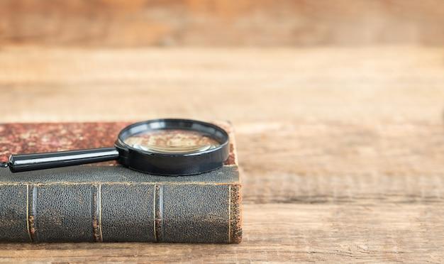 De volta ao conceito de escola e educação livro e lupa em um fundo de madeira e lugar para texto