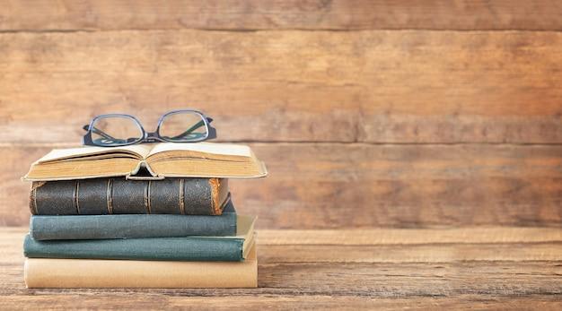 De volta ao conceito de escola e educação livros e óculos no livro aberto sobre um fundo de madeira e lugar para texto