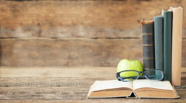 De volta ao conceito de escola e educação livros óculos e maçã no fundo de madeira e lugar para texto