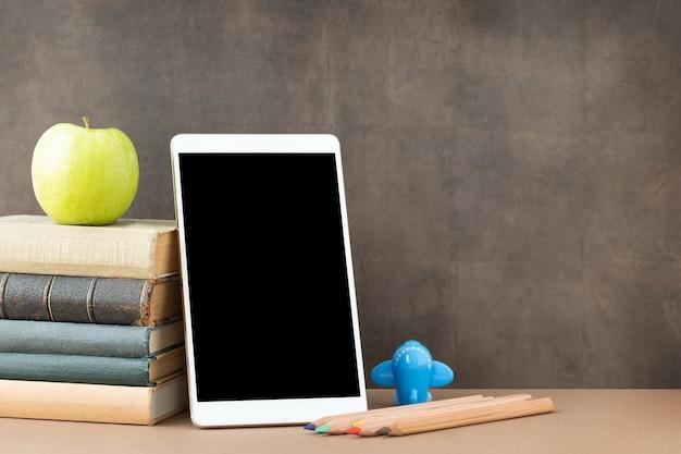 De volta ao conceito de escola e educação o tablet com tela preta pilha de livros canetas maçã e avião perto do quadro-negro e local para texto