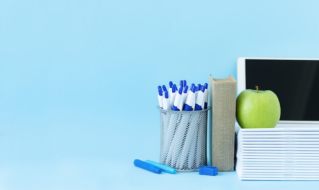 De volta ao conceito de escola e educação papelaria para estudos canetas lápis cadernos livro laptop e maçã verde sobre fundo azul e lugar para texto