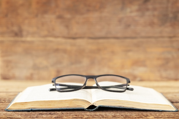 De volta ao conceito de escola e educação um óculos no livro aberto sobre um fundo de madeira e um lugar para texto