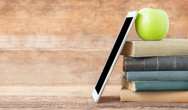 De volta ao conceito de escola e educação uma pilha de livros tablet e maçã verde no fundo de madeira