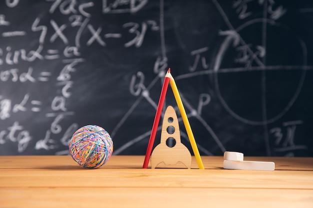 De volta ao conceito de escola. foguete e lápis na frente do quadro-negro da sala de aula