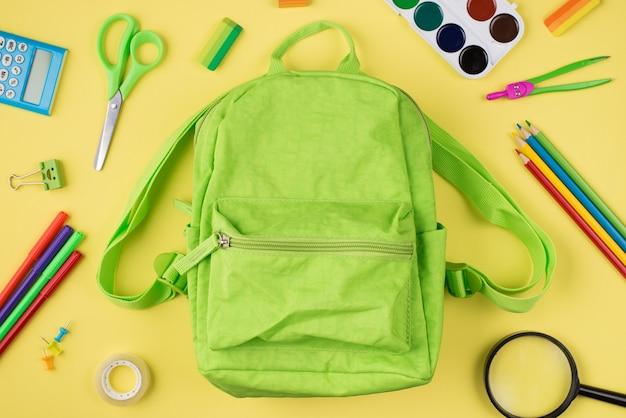 De volta ao conceito de escola. foto de visão aérea superior acima de uma mochila verde e papel de carta colorido isolado em fundo amarelo