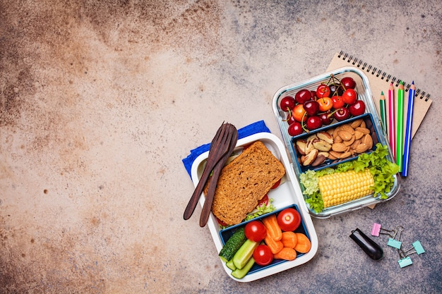 De volta ao conceito de escola. lancheira com alimentos frescos saudáveis. sanduíche, legumes, frutas e nozes em um recipiente para comida, fundo escuro.