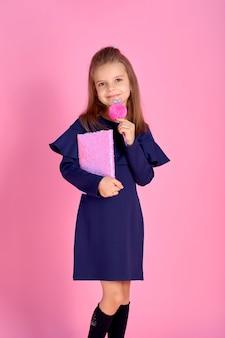 De volta ao conceito de escola meio virado foto retrato de adorável confiante linda garota inteligente com caderno usando uniforme escolar vestido rosa brilhante mochila isolada