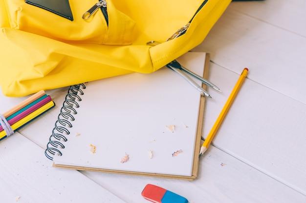 De volta ao conceito de escola. mochila amarela com bloco de notas e artigos de papelaria em um espaço de madeira.