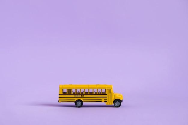 De volta ao conceito de escola. ônibus escolar amarelo tradicional em roxo