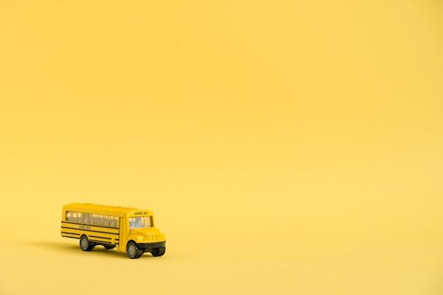 De volta ao conceito de escola. ônibus escolar de modelo de brinquedo amarelo.