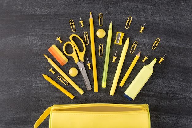 De volta ao conceito de outono de escola. foto de visão aérea superior de conjunto de artigos de papelaria amarelos caindo e caixa de lápis isolada no quadro-negro